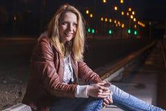 Positive kaukasische Frau in der Lederjacke und in den Blue Jeans Lizenzfreie Stockfotos