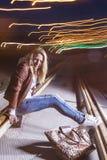 Positive kaukasische Frau in der Lederjacke und in den Blue Jeans Playin lizenzfreie stockfotografie