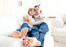 Positive kaukasische Paare, die auf der Couch liegen Stockfotografie