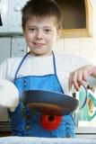 Positive kid with frying-pan Stock Photos