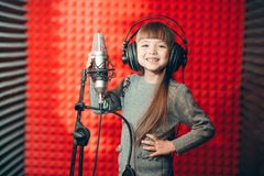 Positive kid posing to the canera during singing classes. Close-up photo stock photography