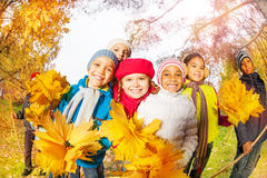 Positive kids with bunch of yellow maple leaves. And rakes standing close in the park during autumn daytime Stock Image