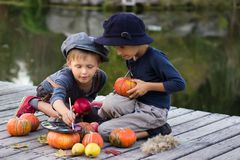 Positive kids paint small Halloween pumpkins. On the river bank Stock Photo