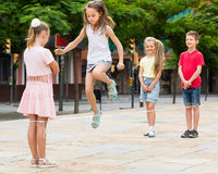 Positive kids playing with chinese jumping rope Stock Images