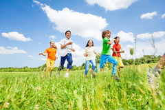 Positive kids playing and running in the field. In summer Royalty Free Stock Image