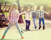 Positive kids playing street football outdoors Stock Photography