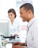 Positive Kollegen, die an einem ihrem Computer arbeiten Lizenzfreies Stockfoto