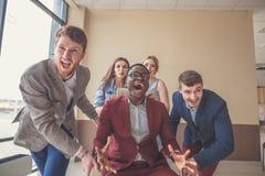Positive Kollegen, die Spaß mit Bürostühlen haben stockfoto