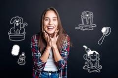Positive lächelnde Frau beim Sehen eines netten kleinen Welpen Lizenzfreie Stockbilder
