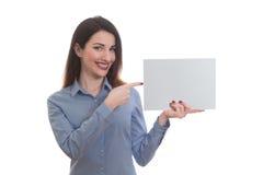 Positive lächelnde Frau im blauen Hemd zeigend auf leeres Stück von Lizenzfreie Stockfotos