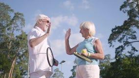Positive lächelnde reife Paare, nachdem Tennis auf dem Tennisplatz gespielt worden ist, der Hände rüttelt und hoch fünf gibt akti stock video