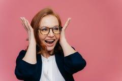 Positive lächelnde Rothaarigefrau bedeckt die Ohren, glücklich, etwas zu hören, das laut ist und lustig, trägt die transparenten  lizenzfreie stockbilder