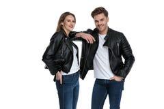 Positive lachende Paare beim Halten ihrer H?nde in ihren Taschen stockfotos