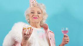 Positive laughing old woman in trendy casual clothes eating pastry. Isolated blue background. Positive emotion and feeling stock video