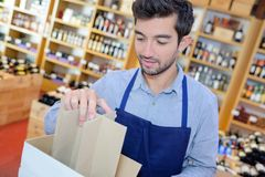Positive liquor store seller wearing apron opening carton. Man Royalty Free Stock Images