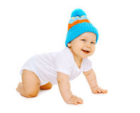 Positive little baby crawls in the knitted hat Stock Photo