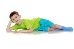Positive little boy lying on the floor Royalty Free Stock Photos