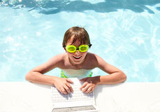 Positive little boy networking in swimming pool Royalty Free Stock Images