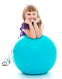 Positive little girl with the blue ball. Stock Photos