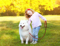 Positive little girl and dog having fun outdoors Stock Photo