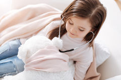 Positive little girl examining fluffy toy with stethoscope Stock Photography