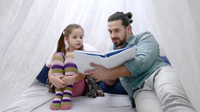Little girl and her father reading a book together stock video