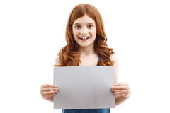 Positive little girl holding  sheet of paper Royalty Free Stock Photo
