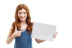 Positive little girl holding  sheet of paper Stock Photo