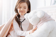 Positive little girl pretending to be a doctor Royalty Free Stock Image