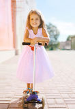Positive little girl riding a scooter. Having fun Stock Images