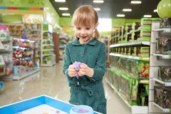 Positive little girl sculpting with plasticine in toy store. Front view of positive little girl sculpting with plasticine in toy store. Funny kid standing in big stock photo