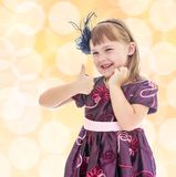 Positive little girl showing thumb up. stock photo