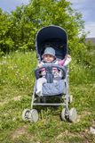Positive little girl in a stroller playing with her legs on a walk. Sunny day baby kicks feet on nature. Positive little girl in a stroller playing with her legs stock image