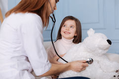 Positive little girl visiting a doctor with her fluffy toy Stock Photography