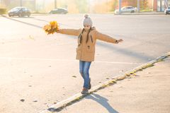 Positive little girl walking on the curb with maple leaves in her hand and trying to keep her balance. Autumn cityscape stock photography