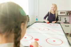 Positive little girls having fun in games room