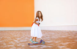 Positive little joyful girl in dress on the scooter. In the city Stock Photos