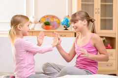 Positive little sisters clapping their hands Royalty Free Stock Photo