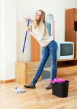 Positive long-haired girl washing parquet  with mop Stock Images