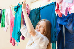 Positive long-haired housewife drying clothes Royalty Free Stock Image