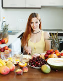 Positive long-haired woman making chopped fruit salad Stock Images