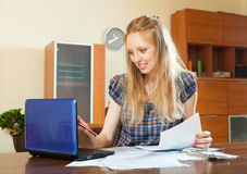 Positive long-haired woman working with  documents and laptop Stock Image