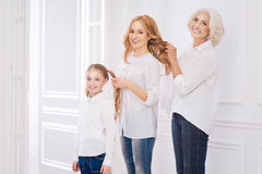 Positive loving family members making hairstyles for each other Stock Image