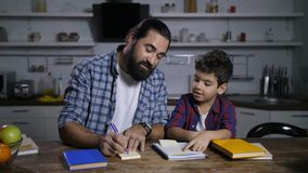 Positive father giving housework tasks to his son stock video
