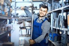 Positive männliche Arbeitskraft, die verschiedene Werkzeuge zeigt Stockfotos