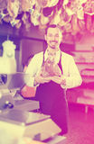 Positive male assistant showing piece of meat. In butcher's store Stock Images