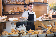Positive male bakery employee offering pastry. Positive male bakery employee offering different pastry for sale Royalty Free Stock Image