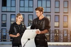 Positive male coach showing the working of EMS device to a fit pretty girl royalty free stock photos
