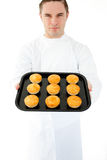 Positive male cook holding muffin Stock Photos