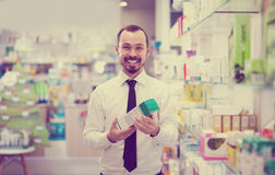 Positive male customer browsing rows of drugs Royalty Free Stock Photos